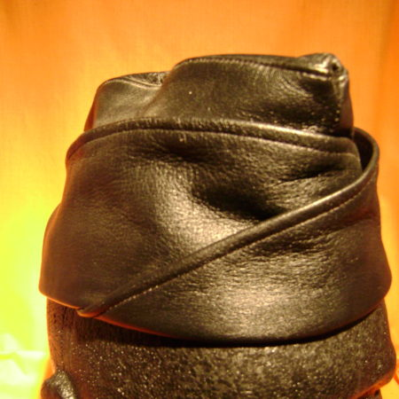"Leather garrison cap,"" ""side cap"" or colloquially as a ""piss-cutter"" or ""cunt cap,"" the cap features a folded crown and straight sides."